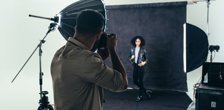 Photographer taking pictures of a model in a studio.