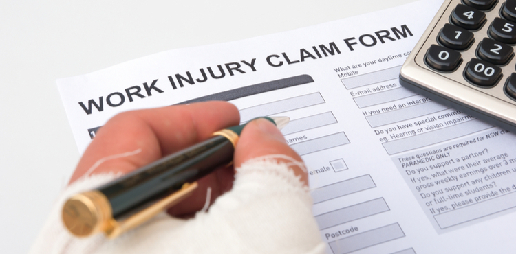 Filing a work injury claim form with bandaged hand.