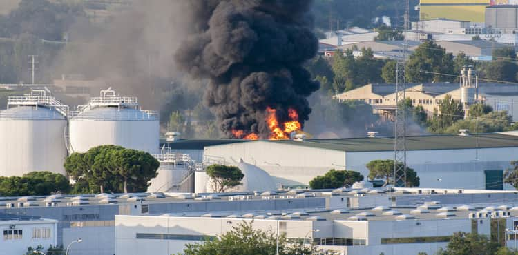 Factory burns and emits black cloud of smoke.