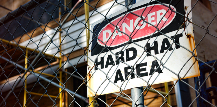 Photo of a danger sign behind a chainlink fence.