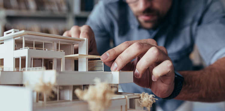 An architect builds a wooden building model.