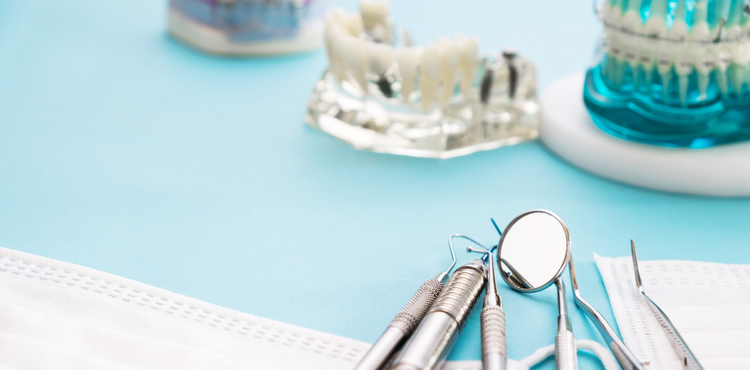 Dental tools on a blue surface.