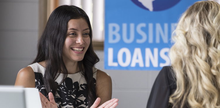 A female business loan worker talking to another woman.