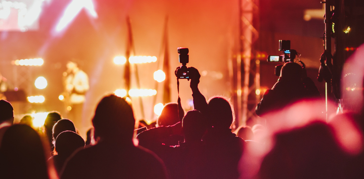 Photographers work in silhouette at a concert.