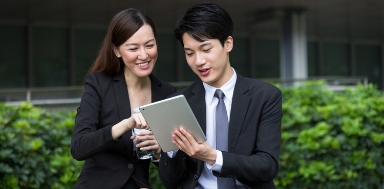Two business people share a tablet in a park.